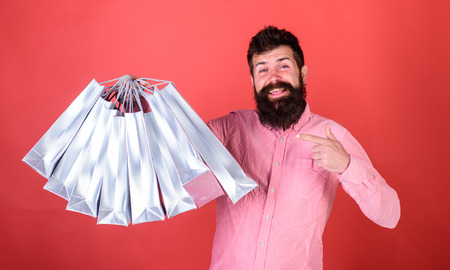 Man with beard and mustache pointing at shopping bags, red background. Hipster on happy face is shopping addicted or shopaholic. Guy shopping on sales season with discounts. Shopping concept
