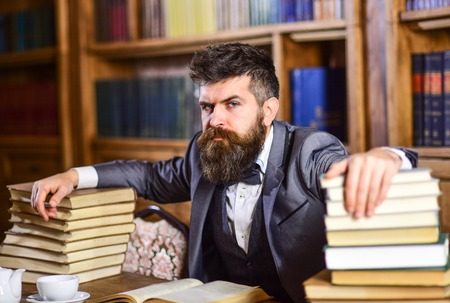 Mężczyzna siedzi przy stole z wieloma książkami.