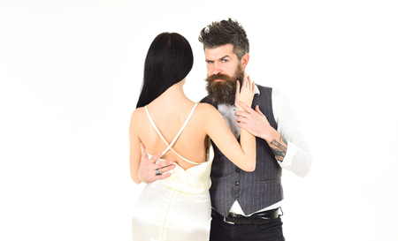 Woman in wedding dress with nude back and man in vest. Hipster with lady dressed up, copy space. Couple in love, bride and groom in elegant clothes, white background. Elegant couple concept