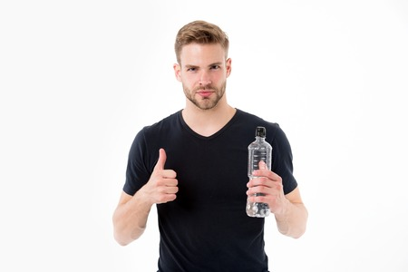 Bearded man show thumbs up with bottle of water. Thirsty man with beard in tshirt hold plastic bottle. Thirst and dehydration concept. Drinking water for health. Like and approval hand sign Stock fotó