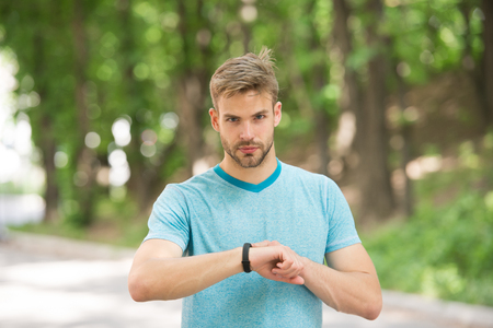 Man athlete on strict face setting up fitness tracker, nature background. Athlete with bristle with fitness tracker or pedometer. Sportsman training with pedometer gadget. Sport gadget concept