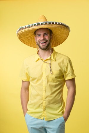 Man on smiling face posing in sombrero hat with hands in pockets, yellow background. Guy with bristle looks festive in sombrero. Fest and holiday concept. Man in festive mood going to celebrate