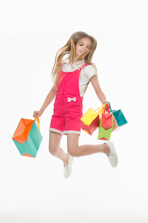 Happy child jump with shopping bags isolated on white. Little girl smile with paper bags. Kid shopper in fashion jumpsuit. Holidays preparation and black friday. Shopping therapy makes her happy.