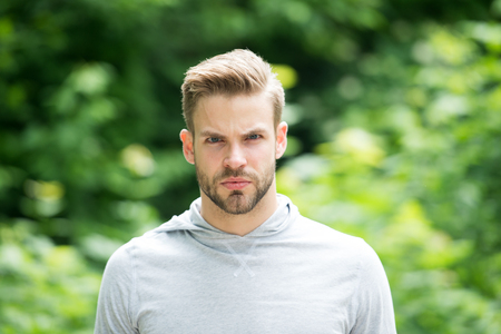 Guy bearded and attractive cares about appearance. Man with bristle on serious face, green nature background, defocused. Metrosexual concept. Man with beard or unshaven guy looks handsome and cool Stock Photo