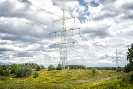 Power towers on natural landscape. Transmission towers on cloudy sky. Electricity pylon structure with power lines. High voltage post outdoor. Energy and ecology