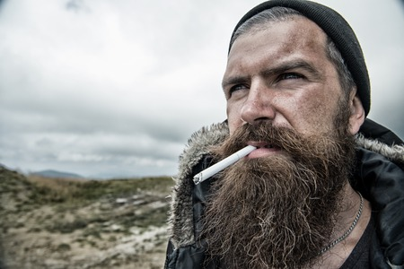 Man with long beard and mustache smoking cigaret. Brutality concept. Hipster on strict face with beard looks brutally while hiking and smoking. Man with brutal bearded appearance, untidy and unshaven