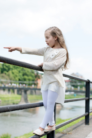 Kid girl with long hair walks near riverside, river on background. Girl child tourist enjoy sightseeing while walks. Vacation concept. Girl or schoolgirl on vacation enjoy travelling and sightseeing