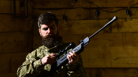 Huntsman concept. Macho on strict face at gamekeepers house. Man with beard wears camouflage clothing, wooden interior background. Hunter, brutal hipster with gun prepare rifle for hunting