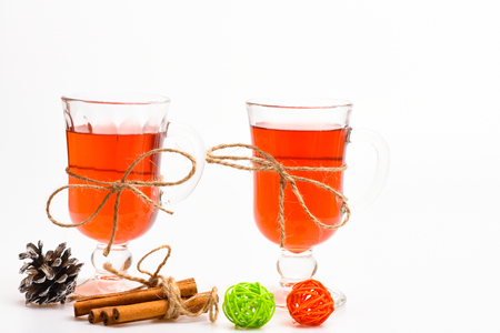 Hot drinks concept. Glasses with mulled wine or cider tied with twine string on white background. Traditional mulled wine with spices. Mulled wine or hot beverage in glasses and cinnamon sticks