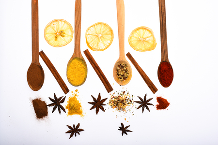 Composition of spoons with spices and dried oranges. Culinary art concept. Spoons filled with kitchen herbs and spices. Spoons with spices as red pepper, curcuma and cinnamon on white background