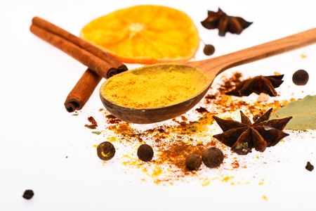 Hot beverages spices kit. Spoon with spices, dried orange, cinnamon stick, cardamom and nutmeg on white background. Spices kit concept. Spices kit for preparing mulled wine or hot beverage, close up