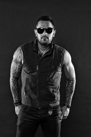 Bearded man with tattoo on strong arms. Tattoo model with beard on unshaven face. Tattooed man with biceps and triceps. Fashion macho in trendy sunglasses. Fashion style and trend, black and white 免版税图像