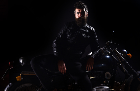 Macho, brutal biker in leather jacket stand near motorcycle at night time, copy space. Biker culture concept. Man with beard, biker in leather jacket lean on motor bike in darkness, black background Stock Photo