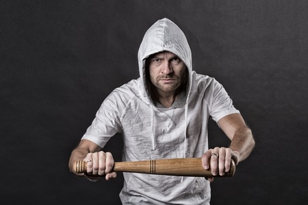 Hooligan hold baseball bat. Bearded man wear hood in hoodie tshirt. Gangster guy threaten with bat weapon. Aggression or anger and violence concept, vintage filter 免版税图像