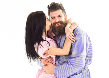 Couple in love hugging in pajama, bathrobe. Couple cuddling, girl kissing macho, isolated on white background. Couple, family on smiling faces happy in morning. Relations goals concept