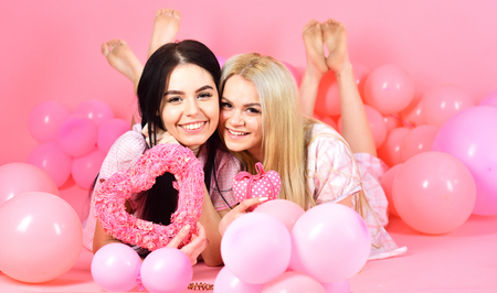 Valentines day concept. Sisters, friends in pajamas at pajamas party. Girls lay near balloons, holds heart toys, pink background. Blonde and brunette on smiling faces dreaming about love and date
