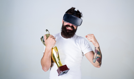 Hipster on happy face squeezing fist as successful gesture. Guy with head mounted display won in virtual game. Winner concept. Man with beard in virtual reality glasses holds goblet, light background