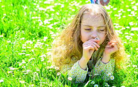 Girl lying on grass at grassplot, green background. Girl on dreamy face spend leisure outdoors. Child enjoy spring sunny weather while lying at meadow. Heyday concept
