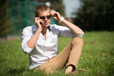 Handsome macho enjoy summer day. Businessman in sunglasses on sunny outdoor. Man relax on green grass. Fashion style and trend. Break time concept