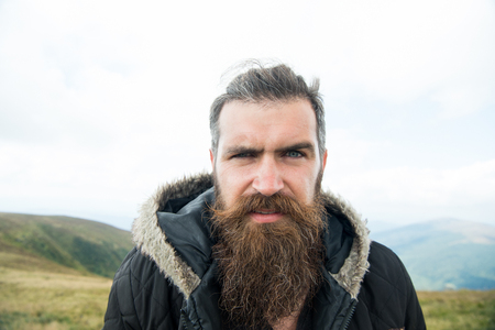 Man with long beard and mustache wears jacket. Hipster on strict face with beard looks brutally while hiking. Hermit concept. Man with brutal bearded appearance, brutal unshaven man looks untidy Banco de Imagens