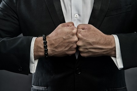 Male fists with swollen veins and bracelet on formal suit background. Confrontation concept. Hand of business person confronts against each other. Symbol of strength of will Stock Photo