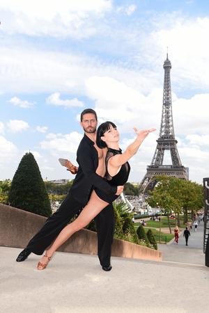 dance couple in front of eifel tower in paris, france. beatuiful ballroom dance couple in dance pose near eifel tower. romantic travel concept