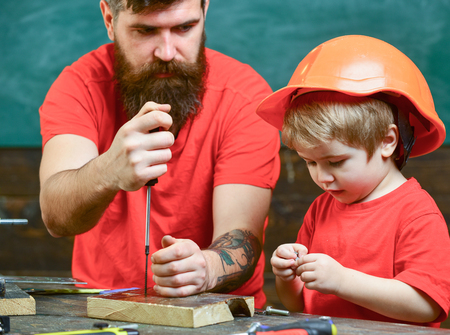 Boy, child busy in protective helmet learning to use screwdriver with dad. Father, parent with beard teaching little son to use tool screwdriver. Handyman and workshop concept