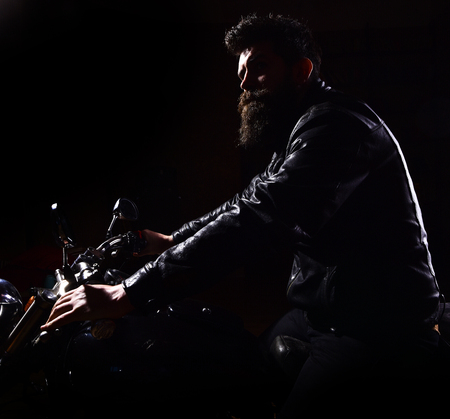 Hipster, brutal biker in leather jacket riding motorcycle at night time, copy space. Night rider concept. Man with beard, biker in leather jacket sitting on motor bike in darkness, black background Stock Photo