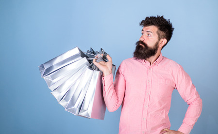 Sale and discount concept. Hipster on serious face carries shopping bags. Guy shopping on sales season with discounts. Man with beard and mustache works as shop assistant, light blue background