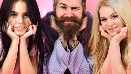 Man with beard and mustache, blonde and brunette girls. Girls with bearded macho, pink background. Best friends concept. Threesome on smiling faces lay near balloons, cheerful company, close up