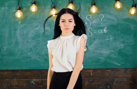 Teacher ready to start lesson, copy space. Woman with long hair in white blouse stands in classroom. Lady teacher on pensive face stands in front of chalkboard. Elite school concept Stock Photo