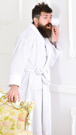 Privacy and secret concept. Man with beard and mustache eavesdrops using cup near wall. Hipster in bathrobe on surprised face secretly listen conversation. Man in white interior spying, eavesdropping Stock Photo