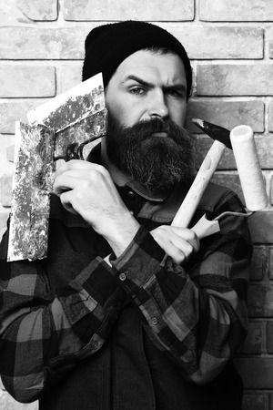 bearded painter man holding various building tools with serious face 写真素材