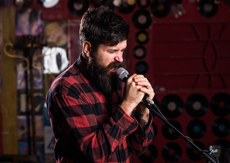 Musician with beard and mustache singing song in karaoke. Stock Photo