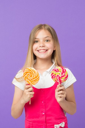 Girl eating big candy on stick or lollipop. Sweet childhood concept. Girl on smiling face holds two giant colorful lollipops in hands, violet background. Kid with long hair likes sweets and treats