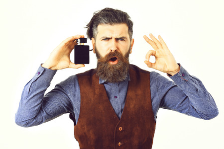 Glamur man hair style. bearded man holding perfume with surprised face