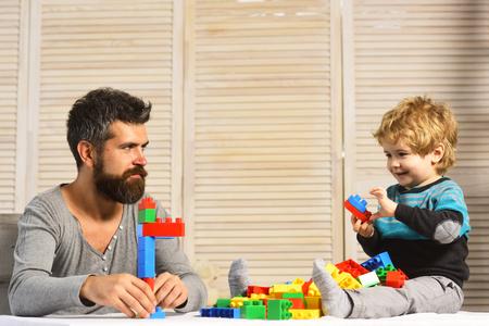 Man met baard en jongen spelen op houten muur achtergrond