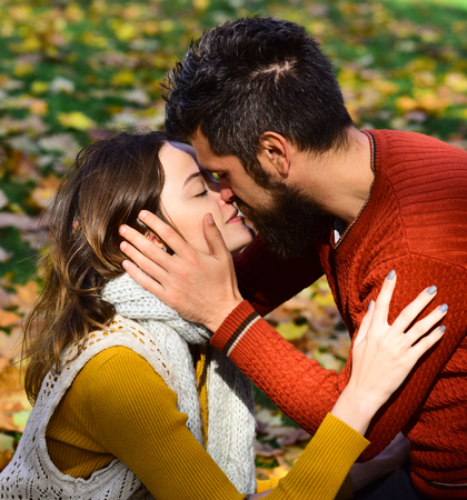 Couple in love with scarves sits on leaves in park