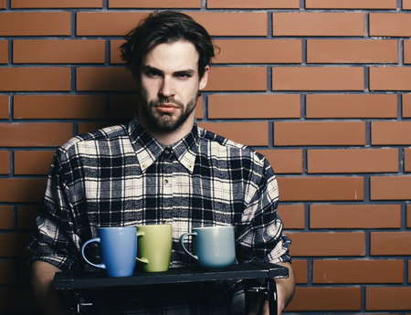 Good morning. handsome guy holding cups on brick wall background