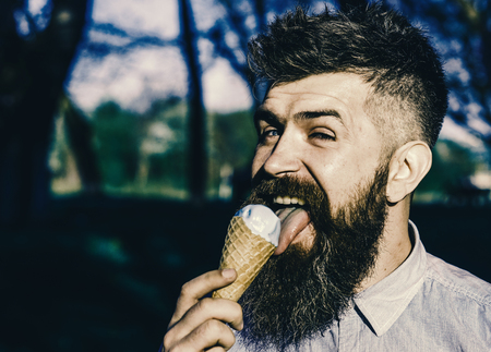 Funny tourist. Man with long beard licks ice cream, close up. Bearded man with ice cream cone. Man with beard and mustache on happy face eats ice cream, nature background, defocused. Chilling concept 版權商用圖片