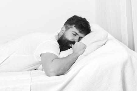 Good morning. Man in shirt laying on bed, white wall on background. Nap and siesta concept. Guy sucking thumb while sleeping on white pillow Stock Photo
