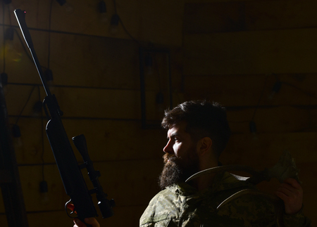 Hunter concept. Macho on strict face at gamekeepers house ready for hunting. Hunter brutal with gun and horns of deer, lighted in darkness. Man with beard wears camouflage clothing, dark background