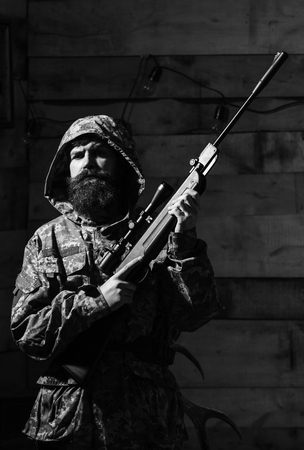 Brave man. Brutal man. Man with beard wears camouflage hooded clothing, wooden interior background. Hunter, brutal hipster with gun prepare rifle for hunting