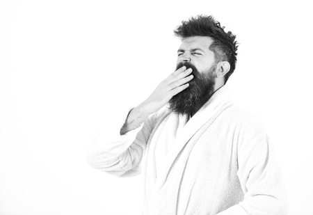 Good morning. Man with beard and mustache yawning and covering mouth with palm, isolated on white background. Guy drowsy with tousled hair Stockfoto