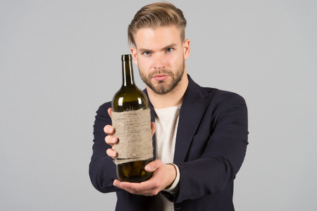 Businessman formal suit confidently welcomes, grey background. Man with bristle looks confident and hospitably while presenting bottle alcohol. Gift concept. Man holds bottle homemade alcohol drink Banco de Imagens