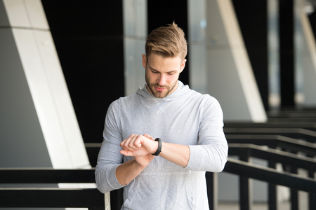 Man athlete on strict face checking fitness tracker, urban background. Athlete with bristle with fitness tracker or pedometer. Sportsman training with pedometer gadget. Sport gadget concept