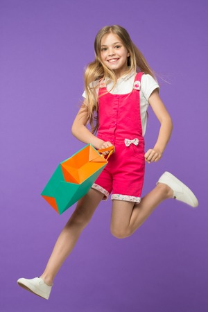 Happy girl jump with shopping bag on violet background. Little child smile with paper bag. Kid shopper in fashion jumpsuit. Holiday preparation and celebration. Shopping and black friday Stock Photo