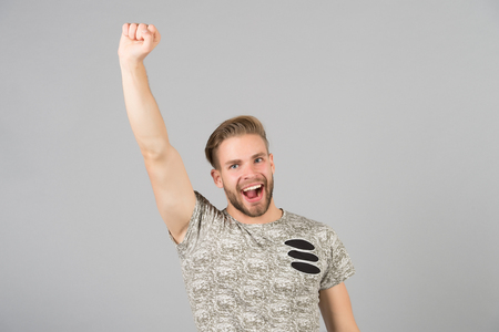 Guy bearded attractive winner lucky raising hand up. Success concept. Man cheerful happy face looks successfully, grey background. Man with beard unshaven guy looks handsome well groomed