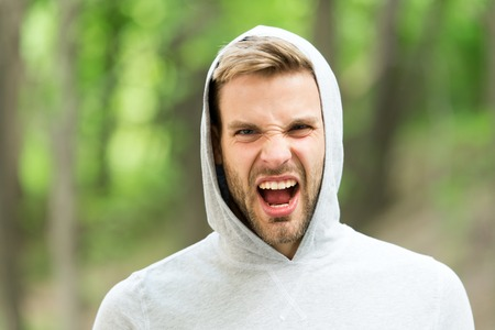 Man with bristle on shouting face, nature background, defocused. Skin care concept. Man with beard or unshaven guy looks handsome hooded. Guy bearded and attractive cares about his appearance