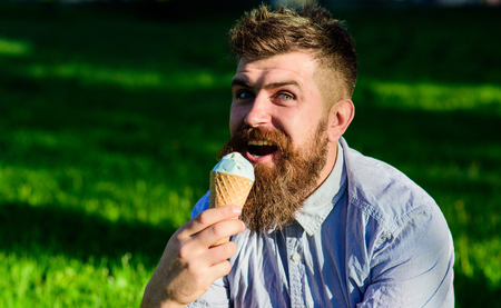 Bearded man with ice cream cone. Man with beard and mustache on happy face enjoy ice cream, grass on background, defocused. Delicacy concept. Man with long beard eats ice cream, while sits on grass 版權商用圖片 - 102657173